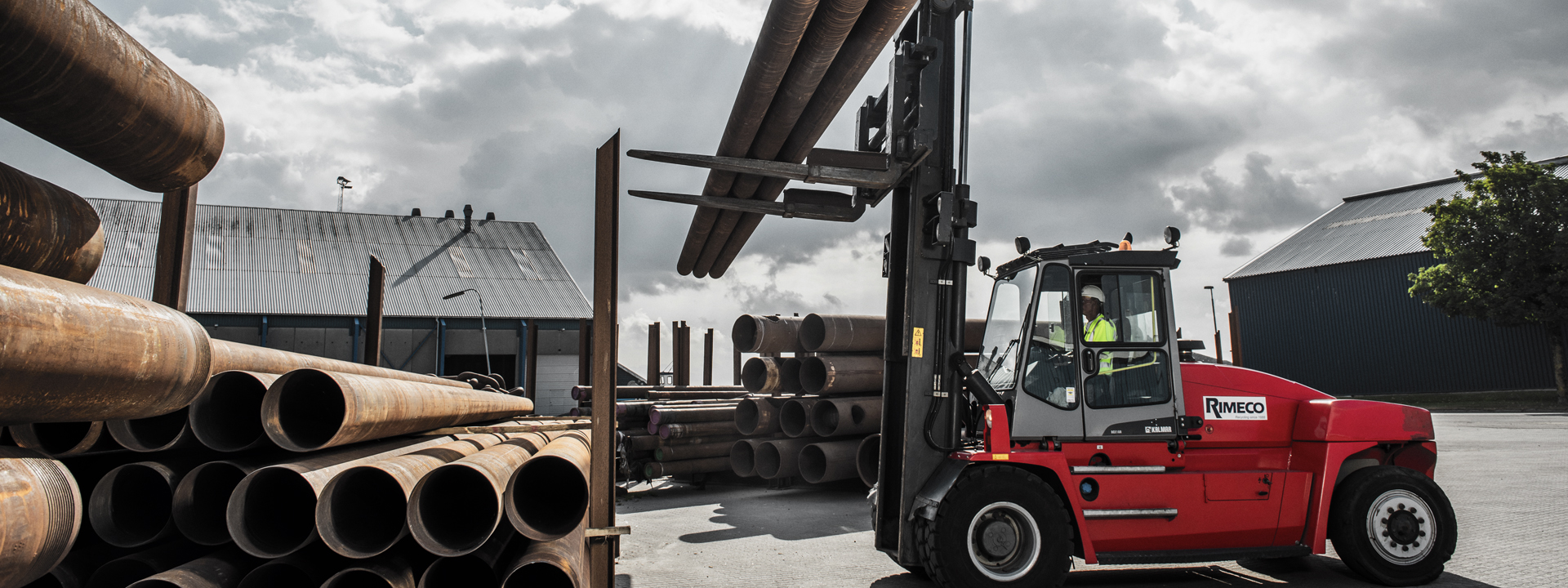 forklift lifting three metalrods